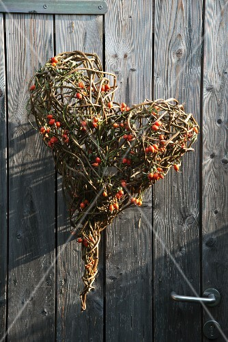 Love-heart formed from twigs and rose hips hung on wooden door