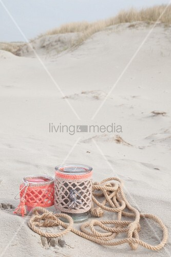 Candle lanterns in pastel crocheted covers on beach