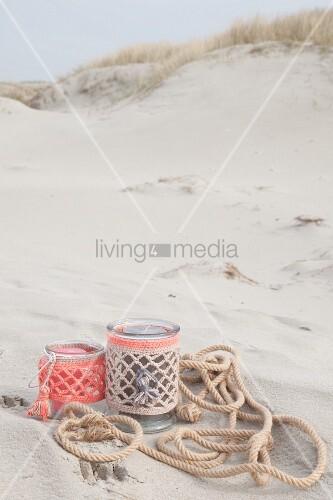 Windlichter mit Häkelhüllen in Pastelltönen am Strand