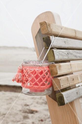 Windlicht mit korallenfarbener Häkelhülle auf Rückenlehne einer Holzbank am Strand