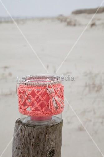 Windlicht mit korallenfarbener Häkelhülle auf Holzpfosten am Strand