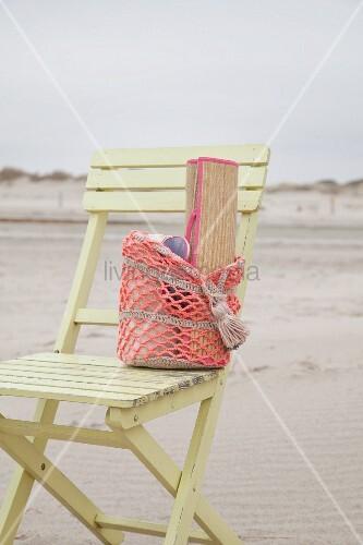 Gehäkelter Strandbeutel mit Bastmatte auf Holzstuhl am Strand