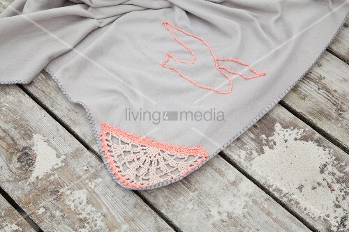 Pale grey picnic blanket with crocheted trim and seagull motif