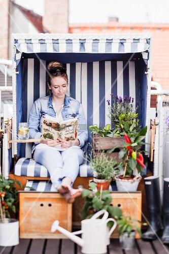 Frau sitzt lesend in einem mit Pflanzen dekorierten Strandkorb auf Balkon