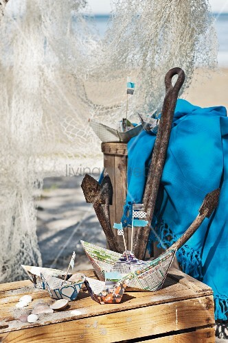 maritime deko aus papierschiffchen anker und fischernetz am strand bild kaufen living4media. Black Bedroom Furniture Sets. Home Design Ideas