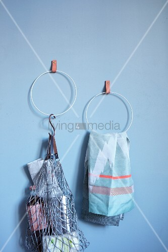 Hand-made towel rings hung on blue wall from leather straps