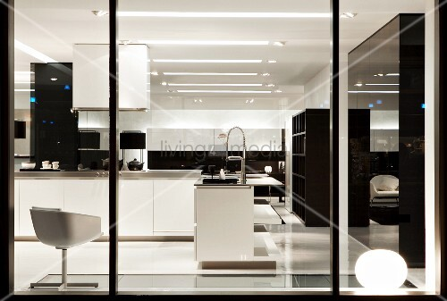 View through shop window of designer kitchen in showroom; white swivel chair and white counter in open-plan kitchen area