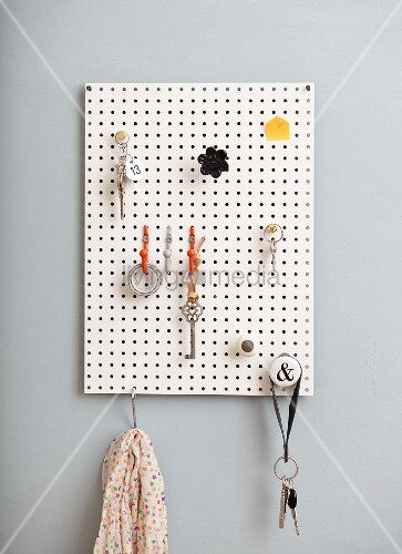 DIY key rack made from white perforated panel and various hooks and knobs