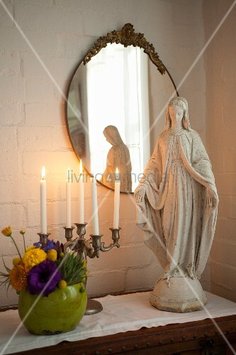 Madonna figurine and brass candelabra on chest of drawers below antique mirror