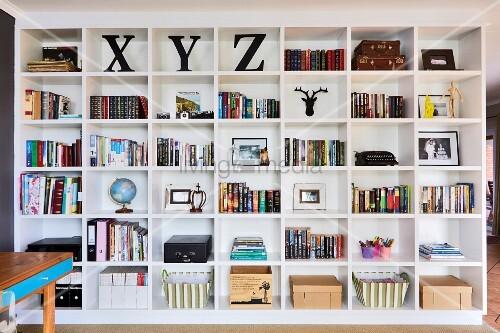 Raumhohes, weisses Regal mit Büchern und Aufbewahrungskörben