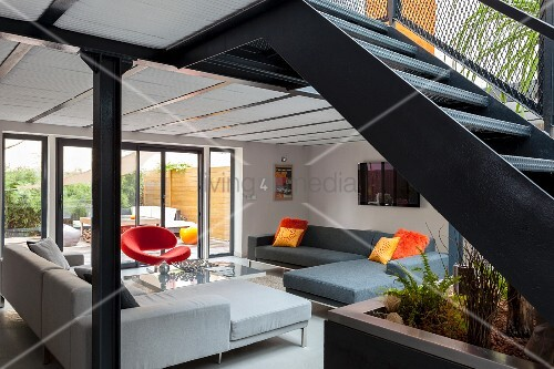 Elegant lounge area with corner sofas in front of terrace doors with steel staircase in foreground