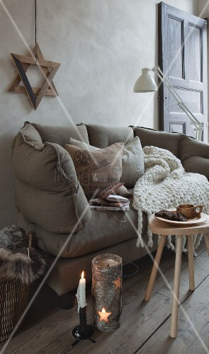 Wooden star (hexagram) above sofa with vintage scatter cushion and knitted blanket; candle lantern wrapped in birch bark with star-shaped cut-outs on wooden floor
