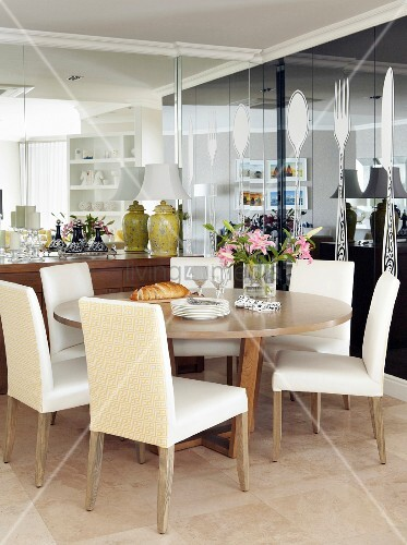 Upholstered chairs at round dining table in corner of room with reflective walls