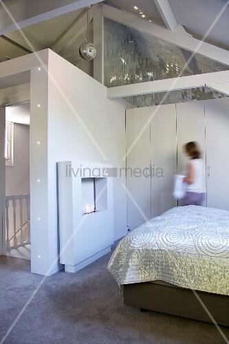 Bett mit glänzender Tagesdecke, Kaminattrappe und Frau vor Einbauschrank im Dachgeschoss-Schlafzimmer