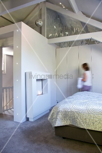 Glossy cover on bed, fake fireplace and woman standing in front of fitted wardrobes in attic bedroom