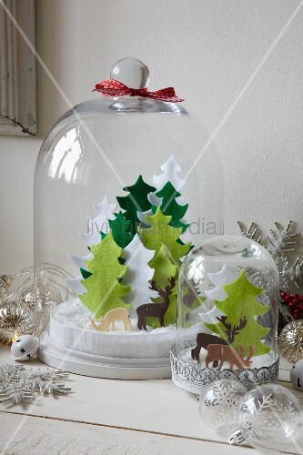 Hand-crafted Christmas scenes with felt Christmas trees and reindeer under glass covers