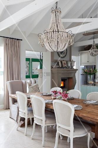 Stühle im Rokoko Stil um Massivholztisch unter antikem Kronleuchter, im Hintergrund Kamin in offenem Wohnraum mit sichtbarer Dachkonstruktion