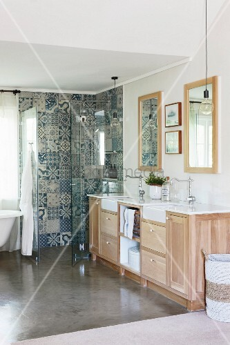 Washstand with vintage-style taps and ornamental tiles in shower area in bathroom