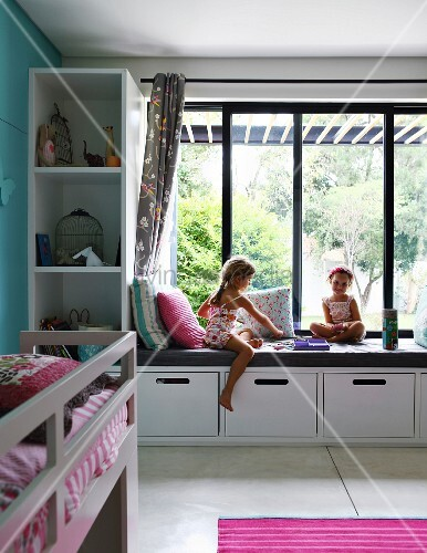 m dchen beim spielen auf eingebauter bank mit polster vor fenster in modernem kinderzimmer. Black Bedroom Furniture Sets. Home Design Ideas