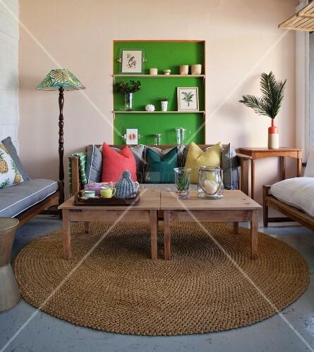 holztische auf rundem sisalteppich vor sitzbank mit kissen. Black Bedroom Furniture Sets. Home Design Ideas