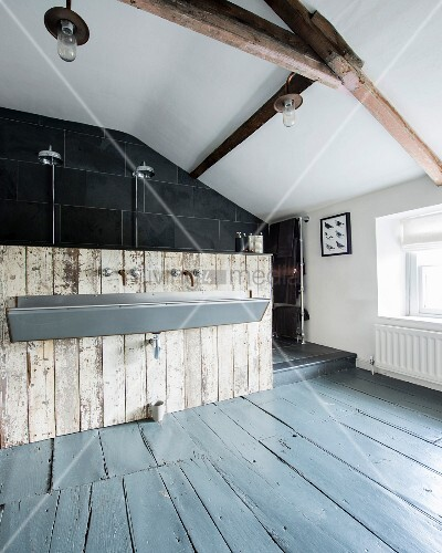 Attic room with purist trough-style sink mounted on vintage board wall in front of open shower area