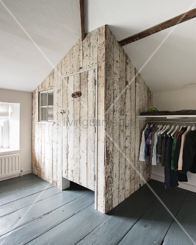 lothes rail next to vintage board shed built into corner of converted attic room