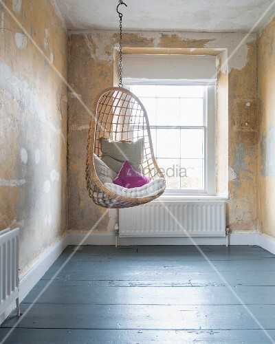 Hanging chair with cushions in front of window in room with patinated walls