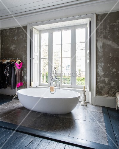 Oval, free-standing designer bathtub on stone tiles in front of bedroom window