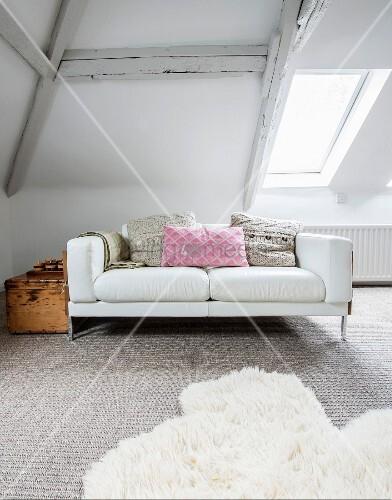 Weisser Zweisitzer mit Kissen und Vintage-Holzkiste im Dachgeschoss