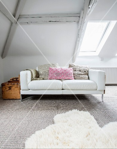 White two-seater sofa with scatter cushions and vintage wooden trunk in attic room