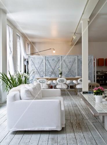 Sofa mit weissem Bezug auf schlichten Dielenboden, im Hintergrund ...