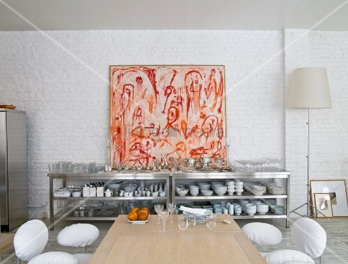 Crockery on stainless steel shelves below modern artwork on whitewashed brick wall
