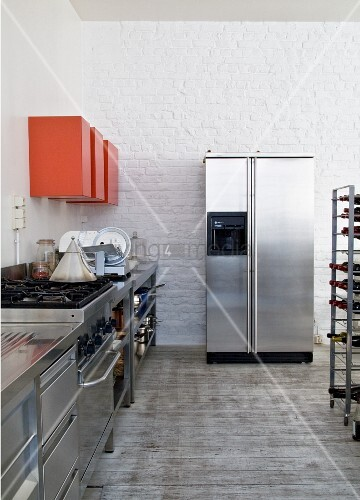 Stainless steel counter, red wall-mounted cabinets and fridge-freezer in kitchen area