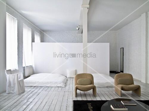 Schlafbereich mit Dielenboden und weiss gestrichener Ziegelwand, im Hintergrund Raumteiler