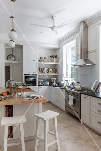 Modern country-house kitchen with white cupboards and free-standing central counter with white-painted bar stools
