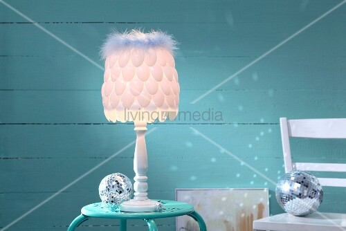 Lampshade hand-made from plastic spoons and feather trim in front of turquoise background