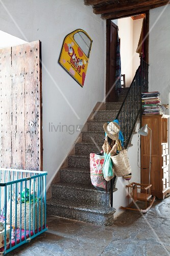 Playpen on stone floor at foot of staircase in foyer