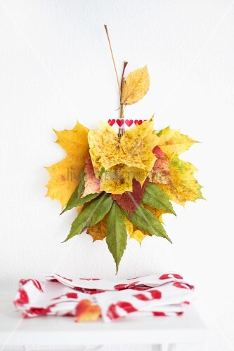 Wall decoration made from autumn leaves and washi table above fabric with pattern of lipstick kisses
