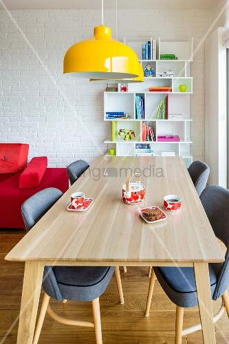Yellow pendant lamps above dining area and bookcase against white brick wall in background