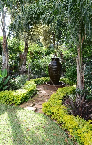 Exotic gardens with amphora-shaped fountain below palm trees
