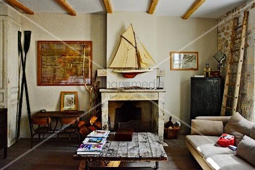 Uberlegen Rustikaler Couchtisch Mit Platte Aus Holzbrettern, Im Hintergrund Offener  Kamin, Darüber Modell Segelboot An Wand, In Schlichtem Wohnzimmer