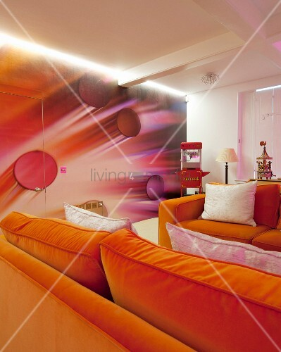 Two orange sofas in front of futuristic 3D wallpaper on wall and hidden door