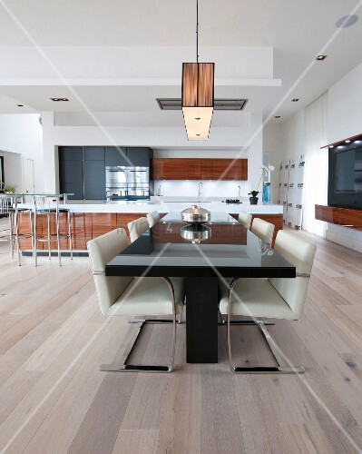 Black dining table and cantilever chairs in open-plan kitchen-dining area