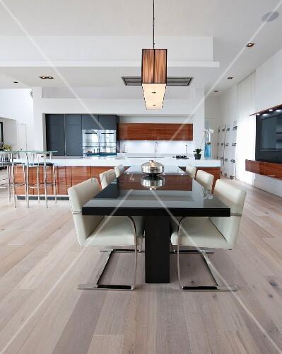 Schwarzer Esstisch mit Schwingstühlen im offenen Koch- und Essbereich