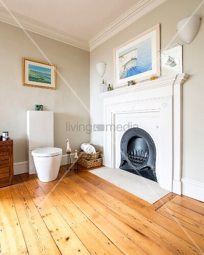 Modern toilet next to open fireplace in corner of bathroom with walls painted pale grey