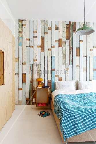 Bed against wallpaper with pattern of old floorboards and plywood fitted wardrobe to one side