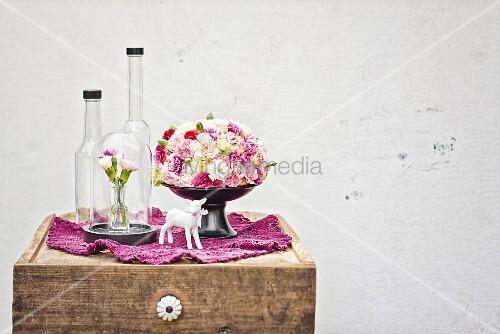 Domed arrangement of summer flowers, glass vessels & china figurine