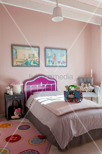 Bed with modern headboard and valance in child's bedroom with pink walls