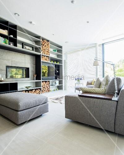 modernes wohnzimmer mit gro er regalwand eingelassenem kamin und holz bild kaufen living4media. Black Bedroom Furniture Sets. Home Design Ideas