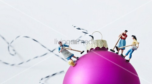 Miniature figurines of women stuck onto pink Christmas bauble